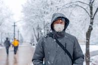 man wearing a face mask outside in a park in the winter