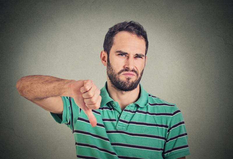 Man with frown holding his thumb down