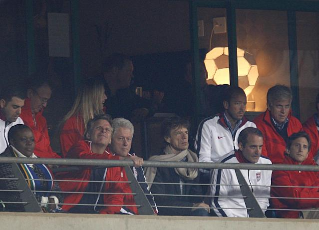 Former US President Bill Clinton (centre left) with veteran British rock star Mick Jagger (centre right) in the stands. (Getty Images)