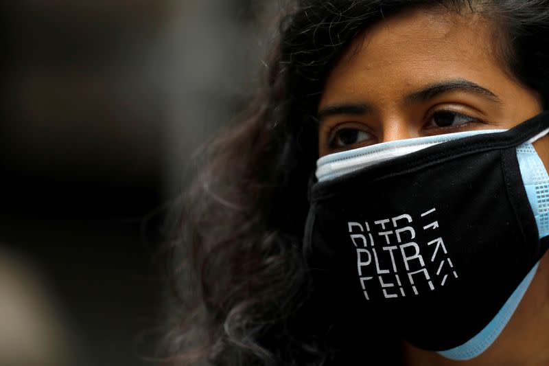 FILE PHOTO: A person wears a Palantir Technologies (PLTR) face mask at the New York Stock Exchange (NYSE) on the day of the company's initial public offering (IPO) in Manhattan, New York City