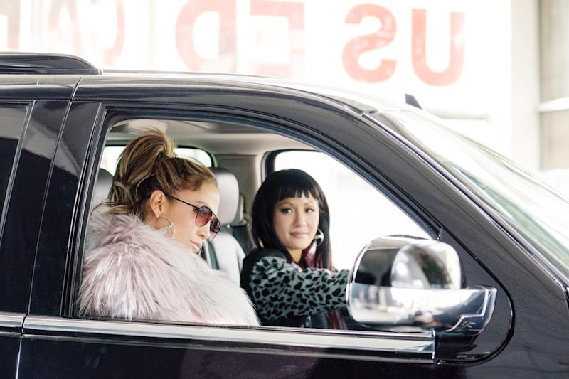 """Jennifer Lopez and Constance Wu listening to """"Gimme More"""" in Hustlers."""