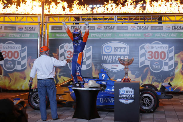 Chip Ganassi, left, looks on as Scott Dixon steps out of his cockpit and onto his car in Victory Lane after winning an IndyCar auto race at Texas Motor Speedway in Fort Worth, Texas, Saturday, June 6, 2020. (AP Photo/Tony Gutierrez)