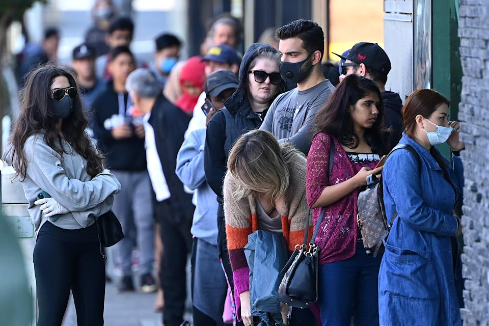 MELBOURNE, AUSTRALIA - MARCH 24: Peopler queue to enter Centrelink on March 24, 2020 in Melbourne, Australia. Non-essential travel has been banned in a bid to stop the spread of COVID-19 in Australia while venues such as bars, clubs, nightclubs, cinemas, gyms and restaurants, along with anywhere people remain static are now closed. Schools are currently open but parents have the option to keep children at home if they wish. There are now 1887 confirmed cases of COVID-19 in Australia and the death toll now stands at eight. (Photo by Quinn Rooney/Getty Images)