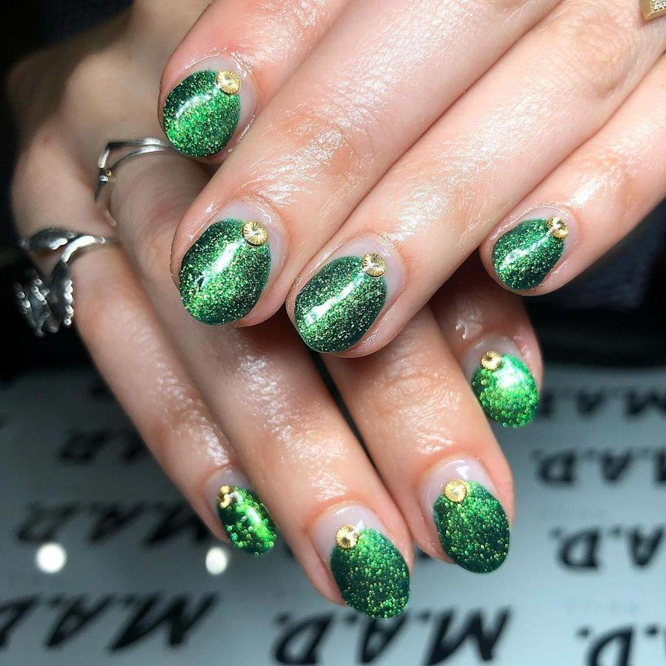 """The secret to these tiny trees is getting the glitter as intense as possible (try <a href=""""https://www.glamour.com/story/how-to-put-on-glitter-nail-polish-correctly?mbid=synd_yahoo_rss"""" rel=""""nofollow noopener"""" target=""""_blank"""" data-ylk=""""slk:this trick"""" class=""""link rapid-noclick-resp"""">this trick</a>). <a href=""""https://shop-links.co/1724785333689561861"""" rel=""""nofollow noopener"""" target=""""_blank"""" data-ylk=""""slk:China Glaze's A Grouchy New Year"""" class=""""link rapid-noclick-resp"""">China Glaze's A Grouchy New Year</a> is the perfect shade for the job."""