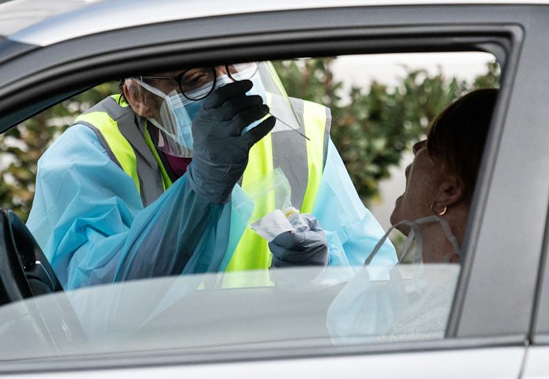 A NSW Health worker dressed in Personal Protective Equipment (PPE) testing a person for COVID-19 from their car at the Crossroads Hotel testing centre in Sydney, Friday, July 17, 2020.