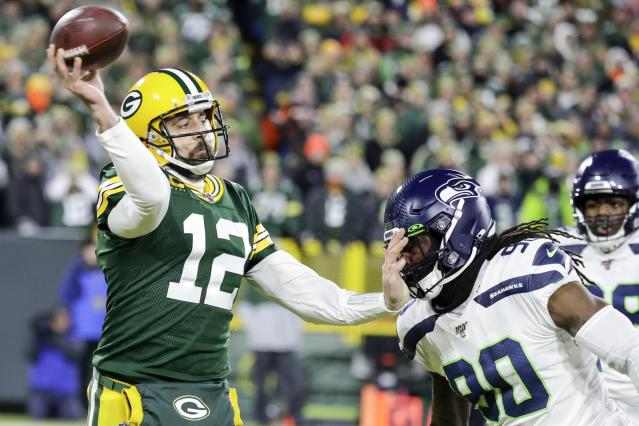 Green Bay Packers' Aaron Rodgers passes while being rushed by Seattle Seahawks' Jarran Reed during the first half of an NFL divisional playoff football game Sunday, Jan. 12, 2020, in Green Bay, Wis. (AP Photo/Darron Cummings)
