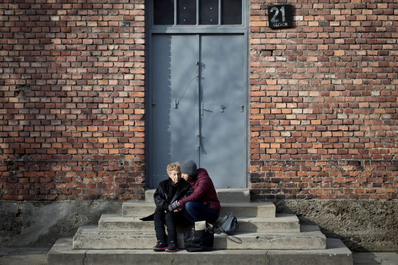 Jona Laks, survivor of Dr. Josef Mengele's twins experiments, and her granddaughter, Lee Aldar sit on the stairs as they visit the Auschwitz death camp in Oswiecim