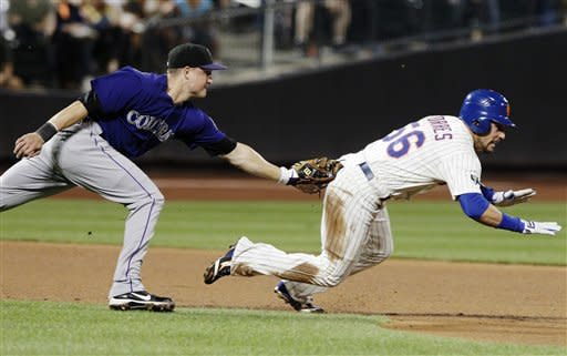Colorado Rockies third baseman Jordan Pacheco, left, tags out New York Mets' Andres Torres, right, during the fifth inning of a baseball game, Tuesday, Aug. 21, 2012, in New York. (AP Photo/Frank Franklin II)