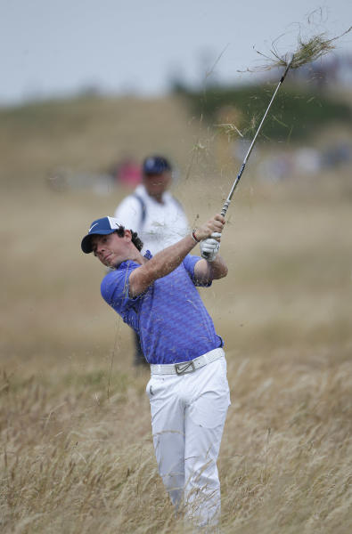 Rory McIlroy of Northern Ireland plays a shot out of the rough on the 18th hole during a practice round ahead of the British Open Golf Championship at Muirfield, Scotland, Wednesday July 17, 2013. (AP Photo/Peter Morrison)