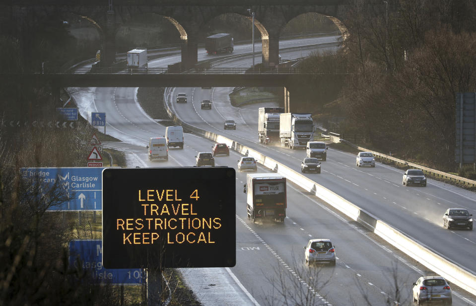 A traffic information board advises drivers to keep their travel to local trips because of coronavirus Level 4 restrictions, as traffic moves along the M80 motorway near Banknock, Scotland, Tuesday Dec. 29, 2020. Scotland has imposed more severe COVID-19 lockdown restrictions for several weeks. (Andrew Milligan/PA via AP)