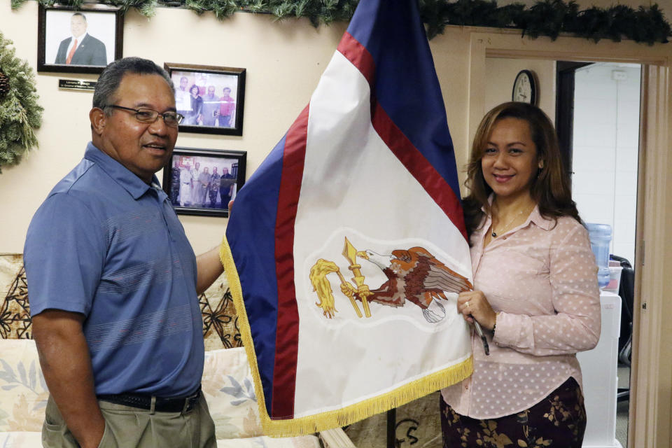FILE - In this Jan. 10, 2020 file photo, Filipo Ilaoa, left, and Bonnelley Pa'uulu pose with the flag of American Samoa at the American Samoa government office in Honolulu. A federal appeals court ruling says U.S. citizenship shouldn't be imposed on those born in American Samoa. The decision reverses a lower court ruling that sided with three people from American Samoa who lived in Utah. They sued to be recognized as citizens. (AP Photo/Jennifer Sinco Kelleher, File)