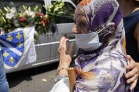 FILE - In this July 9, 2021, file photo, a woman looks at the motorcade transporting the remains of 19 victims of the Srebrenica massacre for reburial at a memorial cemetery in Srebrenica on Sunday, July 11. Twenty-six years after the July 1995 Srebrenica massacre, the only episode of Bosnia's 1992-95 war to be legally defined as genocide, its survivors continue to grapple with the horrors they endured while also confronting increasingly aggressive downplaying and even denial of their ordeal. (AP Photo/Darko Bandic, File)