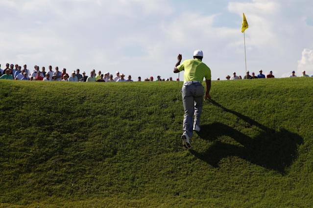 Tiger Woods climbs up out of the bunker on the 14th hole during the first round of the PGA Championship golf tournament on the Ocean Course of the Kiawah Island Golf Resort in Kiawah Island, S.C., Thursday, Aug. 9, 2012. (AP Photo/Chuck Burton)
