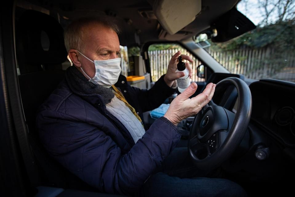 A London taxi driver uses hand sanitiser after dropping off a customerPA