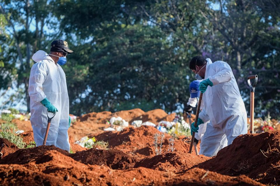 dpatop - 14 October 2020, Brazil, Sao Paulo: Cemetery workers in protective suits shoveling earth at the Vila Formosa cemetery in the Brazilian city of Sao Paulo in the middle of the Corona pandemic. Photo: Lincon Zarbietti/dpa (Photo by Lincon Zarbietti/picture alliance via Getty Images)