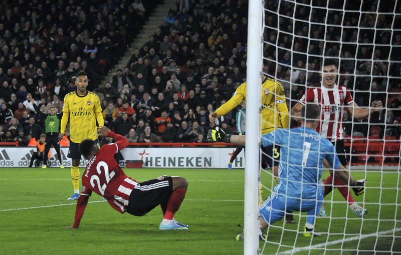Sheffield United's Lys Moussett, left, scores the opening goal during the English Premier League soccer match between Sheffield United and Arsenal at Bramall Lane in Sheffield, England, Monday, Oct. 21, 2019. (AP Photo/Rui Vieira)