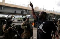 A man gestures as he confronts National Guard members guarding the area in the aftermath of a protest in Minneapolis