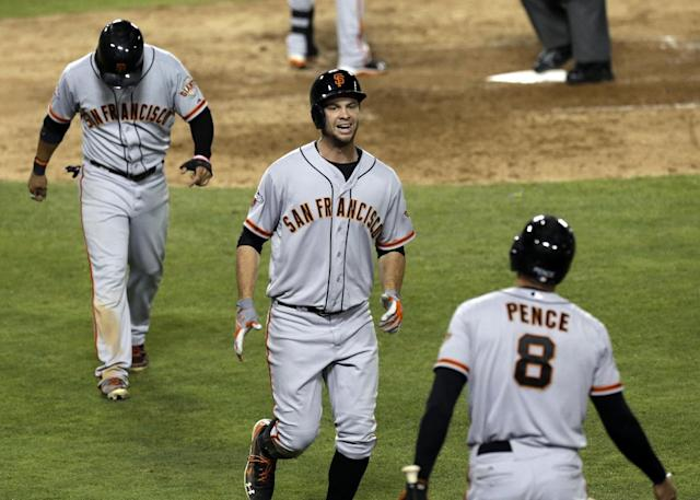 San Francisco Giants on-deck batter Hunter Pence, who had a grand slam in the fifth, greets Brandon Belt, center, and Gregor Blanco, who scored on Belt's home run against the Los Angeles Dodgers in the sixth inning of a baseball game in Los Angeles Saturday, Sept. 14, 2013. (AP Photo/Reed Saxon)