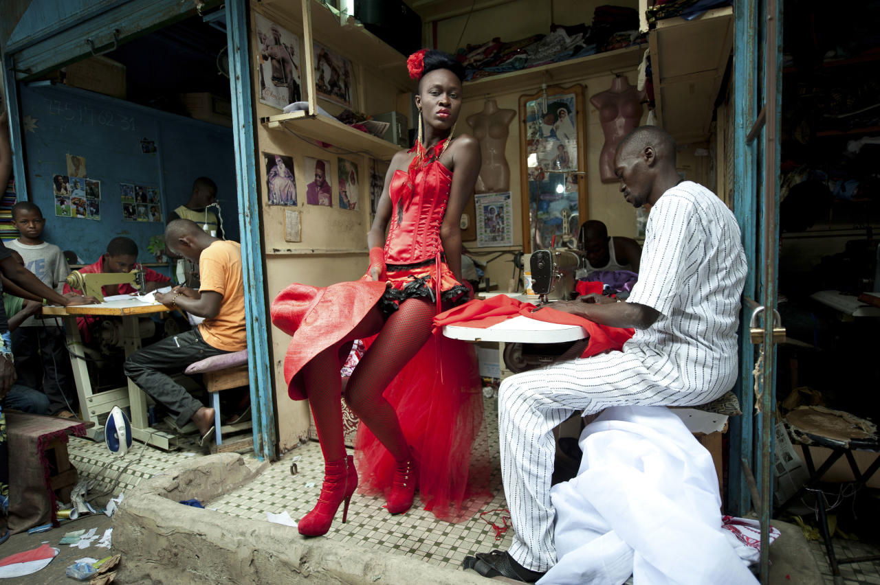 In this photo provided on Friday Feb. 10, 2012 by World Press Photo, the 2nd prize Arts and Entertainment Singles category of the 2012 World Press Photo contest by Vincent Boisot, France, Riva Press for Le Figaro Magazine, shows a model posing in front of tailor stalls in the center of Dakar, Senegal, July 9, 2011. She wears the creation of a designer, Yolande Mancini, participating in the 9th edition of Dakar Fashion Week. (AP Photo/Vincent Boisot/Riva press for Le Figaro Magazine)