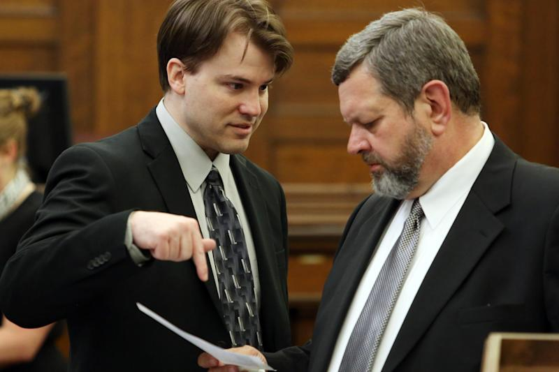 Defendent Brett Seacat, left, talks with his attorney Roger Falk as they look over evidence before the start of his trial on Friday, June 7, 2013, in Kingman, Kan. Seacat is charged with first-degree murder and aggravated arson in the shooting death of his wife, 34-year-old Vashti Seacat. (AP Photo/The Hutchinson News, Travis Morisse, Pool)