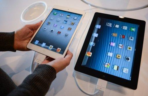 A customer compares an iPad mini (L) to an iPad at an Apple store in Rome. In tablets, Apple's market share has fallen to just over 50 percent from 65 percent in the second quarter as Android devices gain ground, according to IDC figures