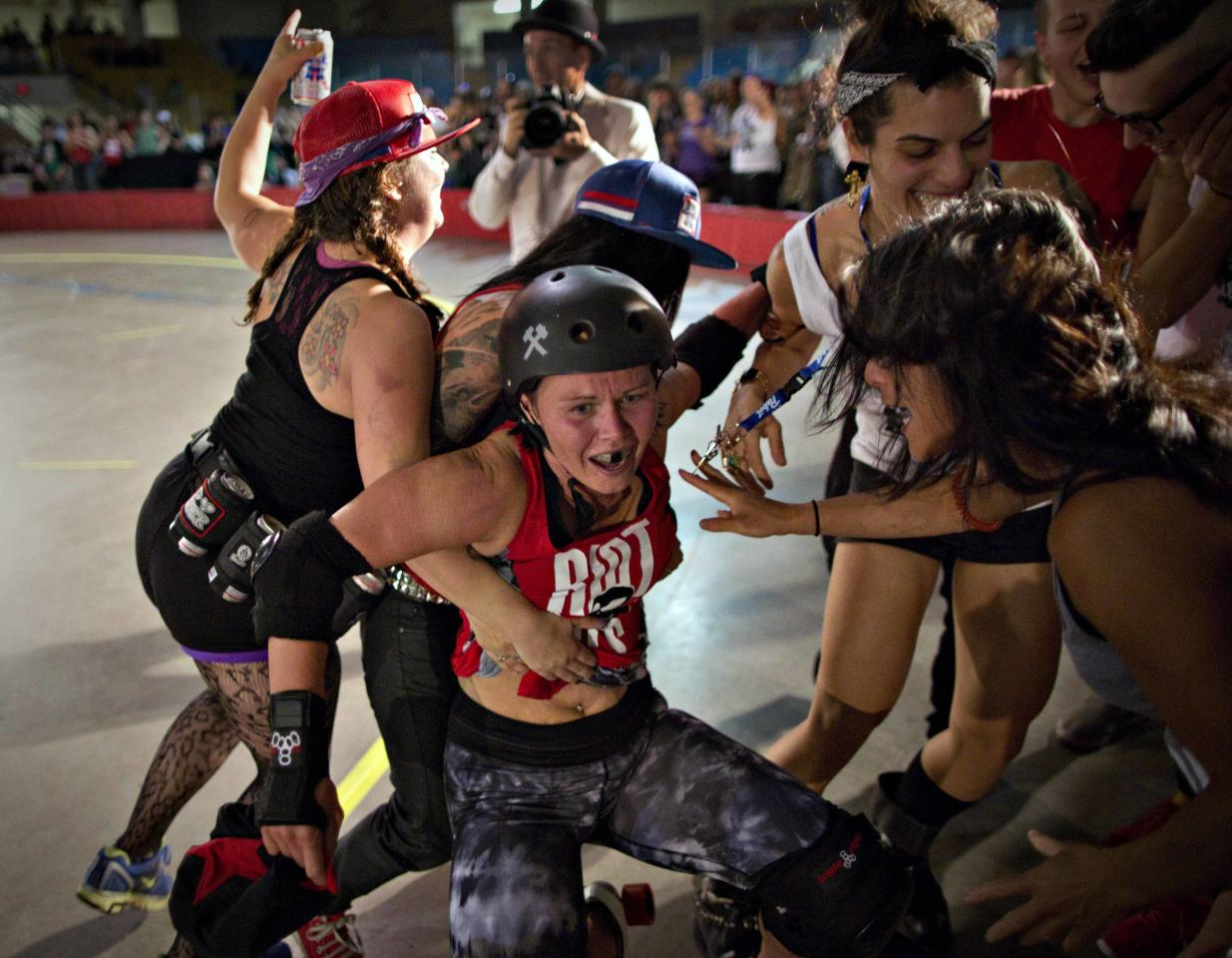 """A player known as """"Justine TimberSkate"""" is mobbed by fans in the closing moments of the Terminal City Rollergirls league championship game in Vancouver, British Columbia September 7, 2013. TimberSkate and her teammates, known as the Riot Girls, won the 2013 championship. REUTERS/Andy Clark (CANADA - Tags: SPORT SOCIETY TPX IMAGES OF THE DAY)"""
