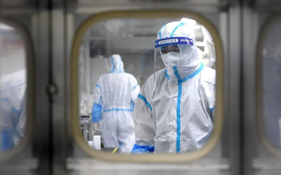 Medical workers in protective suits test nucleic acid samples inside a Huo-Yan (Fire Eye) laboratory of BGI, following new cases in Wuhan, Hubei province, China - China Daily/Reuters