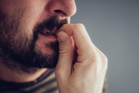 Close-up of a man biting his nails.