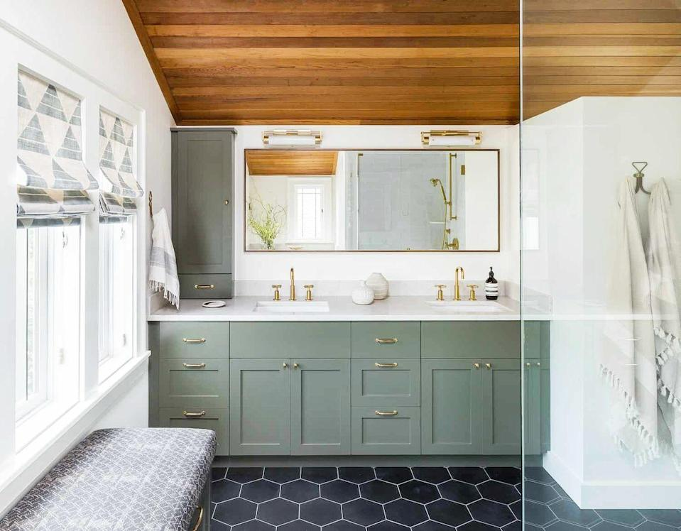 """<p>Installing wood panels vertically will elongate your ceiling, but if you'd rather make a room feel wider, considering arranging them horizontally. This will be especially useful in a smaller space, like a bathroom, as exemplified here. The sloped wood ceiling, mossy green cabinets, and charcoal floor tiles in this bathroom by <a href=""""https://heidicaillierdesign.com/"""" rel=""""nofollow noopener"""" target=""""_blank"""" data-ylk=""""slk:Heidi Caillier"""" class=""""link rapid-noclick-resp"""">Heidi Caillier</a> pay homage to the Queen Anne's surrounding Pacific North West environment. </p>"""