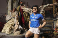 A statuette by Nativity artist Gennaro Di Virgilio portraying soccer legend Diego Armando Maradona with Angel's wing is exposed next to a Nativity scene in his shop in Naples, Italy, Thursday, Nov. 26, 2020. Maradona died Wednesday, Nov. 25, 2020 in Buenos Aires. (AP Photo/Salvatore Laporta)