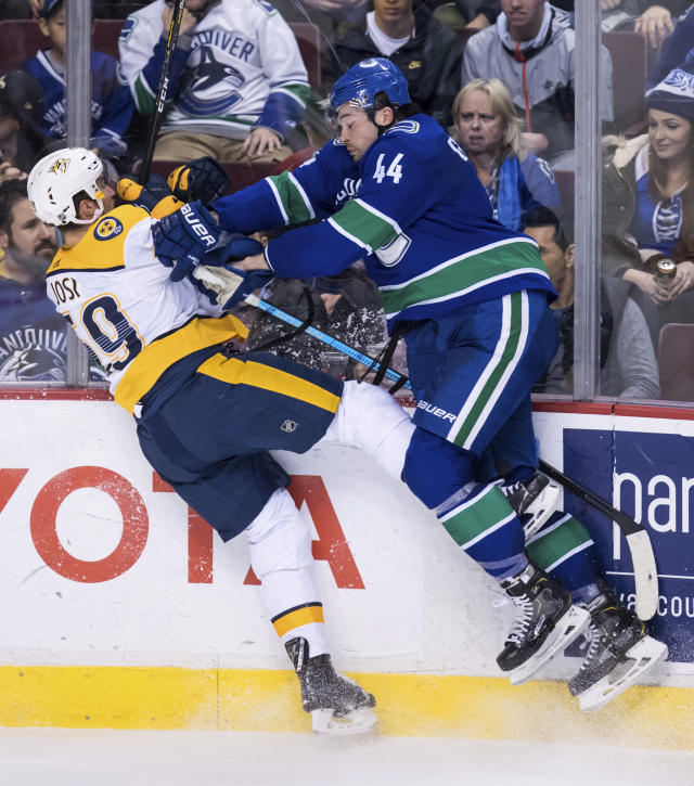 Vancouver Canucks' Erik Gudbranson, right, checks Nashville Predators' Roman Josi, of Switzerland, during the second period of an NHL hockey game Thursday, Dec. 6, 2018, in Vancouver, British Columbia. (Darry Dyck/The Canadian Press via AP)