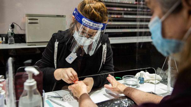 PHOTO: A worker wearing a protective mask and face shield gives a customer a manicure behind a plastic barrier at a nail salon in Syracuse, New York, June 15, 2020. (Maranie Staab/Bloomberg via Getty Images)