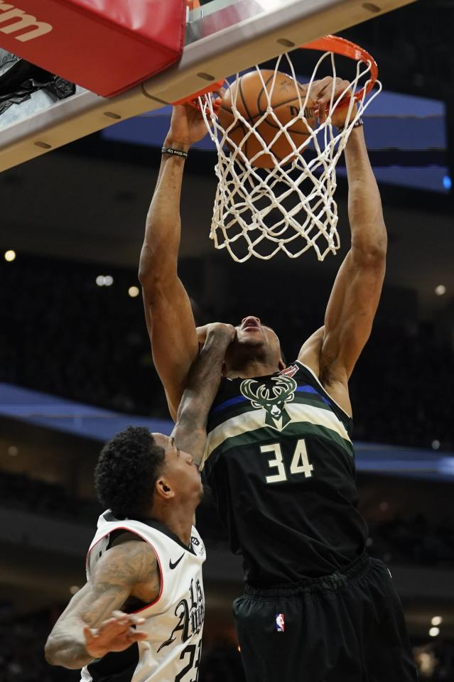 Milwaukee Bucks' Giannis Antetokounmpo dunks over Los Angeles Clippers' Lou Williams during the second half of an NBA basketball game Friday, Dec. 6, 2019, in Milwaukee. (AP Photo/Morry Gash)