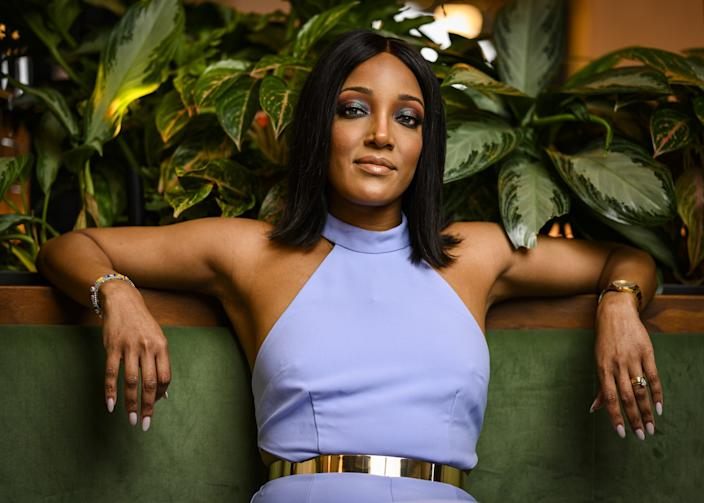 Singer Mickey Guyton lounges on a green chair in a lavender halter dress