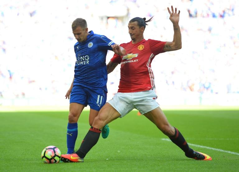Manchester United's Swedish striker Zlatan Ibrahimovic (R) tackles Leicester City's English midfielder Marc Albrighton (L) during the FA Community Shield football match between Manchester United and Leicester City on August 7, 2016