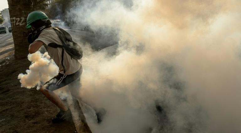 A demonstrator runs away from a tear gas canister thrown by riot police during clashes which erupted during a protest against the government of Chilean President Sebastian Pinera, in Santiago on January 24, 2020 (AFP Photo/Martin BERNETTI)