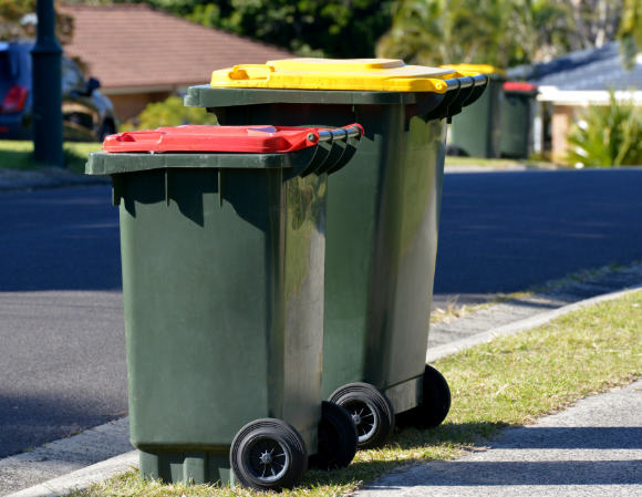 Two rubbish bins on the roadside in Victoria - a red bin and yellow recycling bin.