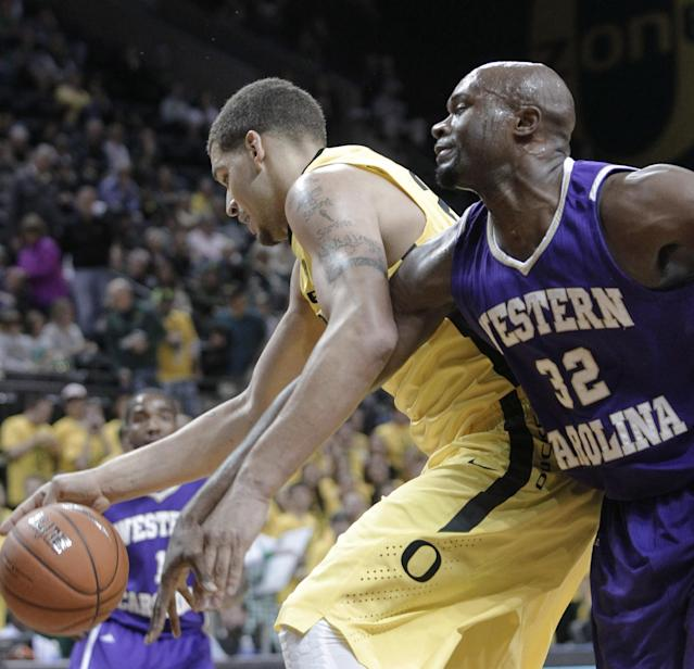 Western Carolina forward Tawaski King, right, reaches in on Oregon center Waverly Austin during the first half of an NCAA college basketball game in Eugene, Ore., Wednesday, Nov. 13, 2013. (AP Photo/Don Ryan)
