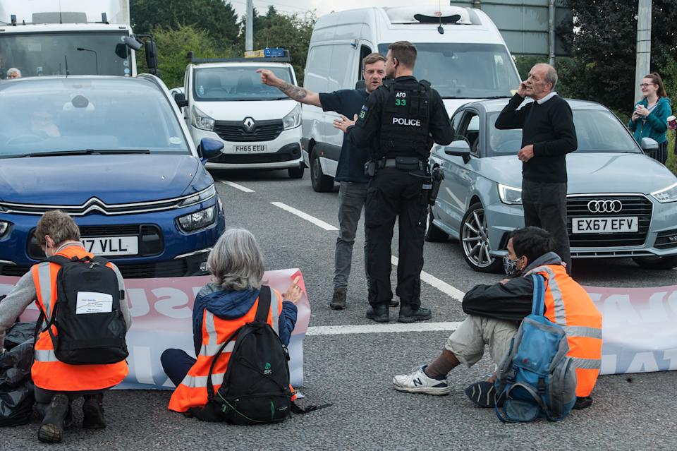 ESSEX, ENGLAND - SEPTEMBER 17: Police arrive on the scene as protesters from the Insulate Britain pressure group block a roundabout near Stansted Airport on September 17, 2021 in Stansted, Essex. (Photo by Guy Smallman/Getty Images)