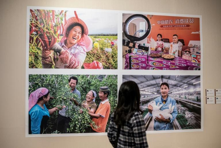 A woman views a photo exhibition featuring images taken in China's northwestern Xinjiang region, organised by the China Photographers Association, in Beijing