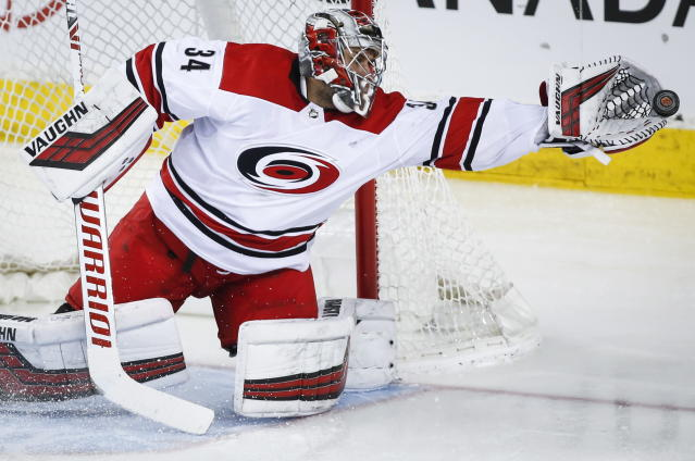 Carolina Hurricanes goalie Petr Mrazek, of the Czech Republic, grabs for the puck during second period NHL hockey action against the Calgary Flames, in Calgary, Tuesday, Jan. 22, 2019. (Jeff McIntosh/The Canadian Press via AP)