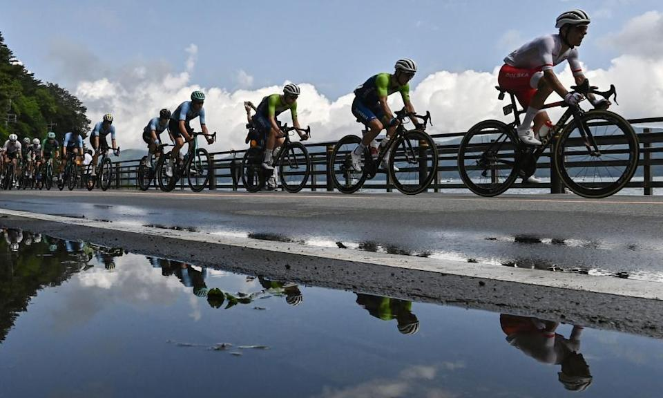 Cyclists in the peloton are reflected on a puddle as they ride past Yamanaka Lake.