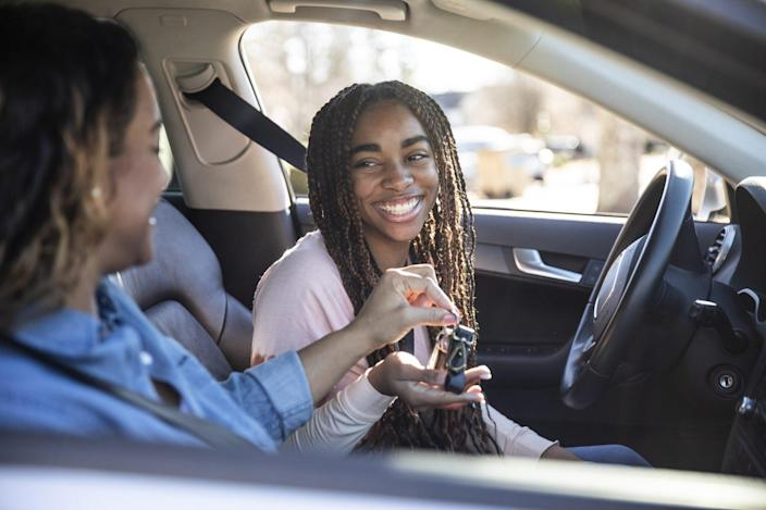 An image of a mom handing car keys to her teenage daughter.