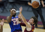 New York Knicks' Mitchell Robinson, left, loses control of the ball as he drives to the basket against Cleveland Cavaliers' Cedi Osman during the second half of an NBA basketball game Friday, Jan. 15, 2021, in Cleveland. Cleveland won 106-103. (AP Photo/Tony Dejak)