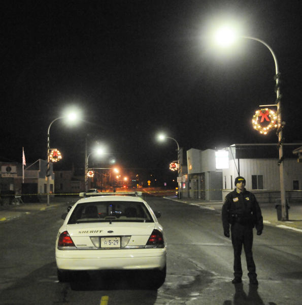 A Stearns County Sheriff's deputy stands at a perimeter at the corner of Main Street and Third Avenue in Cold Spring, Minn., early Friday, Nov. 30, 2012, after a Cold Spring police officer was fatally shot while conducting a routine check near a bar. (AP Photo/The St. Cloud Times, Eric Stromgren) NO SALES