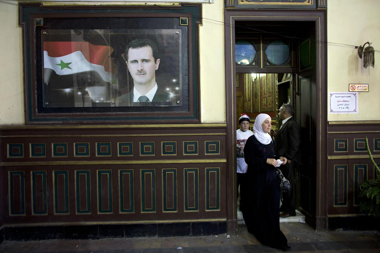 A Syrian woman leaves a polling station in an old train station in Damascus, Syria, Tuesday June 3, 2014. Polls opened in government-held areas in Syria amid very tight security Tuesday for the country's presidential election, a vote that President Bashar Assad, on the poster, is widely expected to win. (AP Photo/Dusan Vranic)