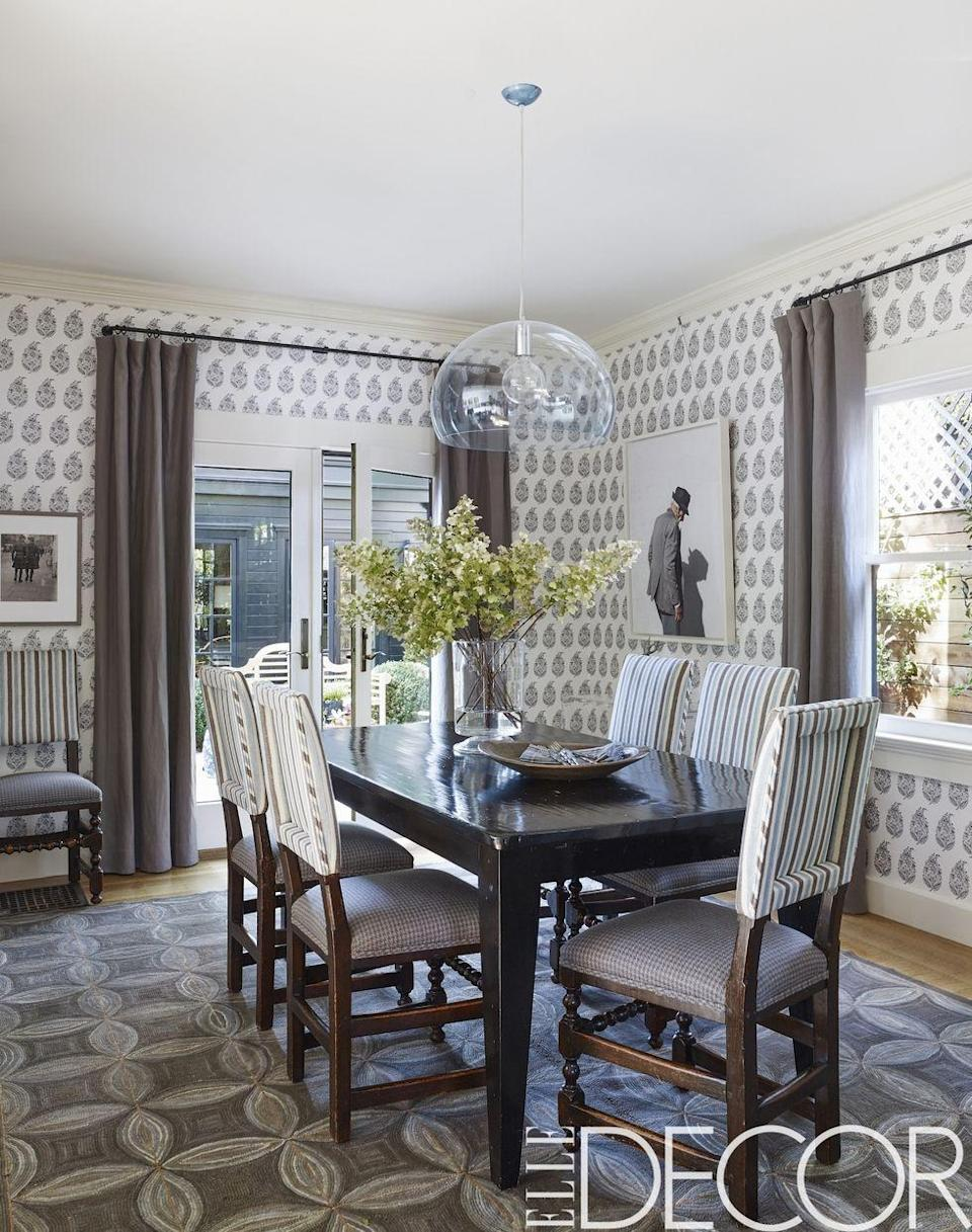 """<p>The dining room in an <a href=""""https://www.elledecor.com/design-decorate/house-interiors/a9113169/oakland-beautiful-homes/"""" rel=""""nofollow noopener"""" target=""""_blank"""" data-ylk=""""slk:eclectic Oakland home"""" class=""""link rapid-noclick-resp"""">eclectic Oakland home</a> is lined with the patterned wallpaper by <a class=""""link rapid-noclick-resp"""" href=""""https://www.fschumacher.com/"""" rel=""""nofollow noopener"""" target=""""_blank"""" data-ylk=""""slk:Schumacher"""">Schumacher</a>. The bold pendant light is by <a class=""""link rapid-noclick-resp"""" href=""""http://shopkartell.com/"""" rel=""""nofollow noopener"""" target=""""_blank"""" data-ylk=""""slk:Kartell"""">Kartell</a>, the vintage hooked rug is American, and the photograph is by <a class=""""link rapid-noclick-resp"""" href=""""http://www.katygrannan.com/"""" rel=""""nofollow noopener"""" target=""""_blank"""" data-ylk=""""slk:Katy Grannan"""">Katy Grannan</a>.</p><p><em>Kerala Paisley Wallpaper, $144.90<br></em><a class=""""link rapid-noclick-resp"""" href=""""https://www.mahoneswallpapershop.com/product/5005280-schumacher-wallpaper-kerala-paisley?gclid=CjwKCAjw8NfrBRA7EiwAfiVJpZHf9FDRtfrvLznkLTv7LtNrik9X5g1pPzpbBDYO6yV3SUea5-J5axoCFDsQAvD_BwE"""" rel=""""nofollow noopener"""" target=""""_blank"""" data-ylk=""""slk:Shop the Look"""">Shop the Look</a></p>"""