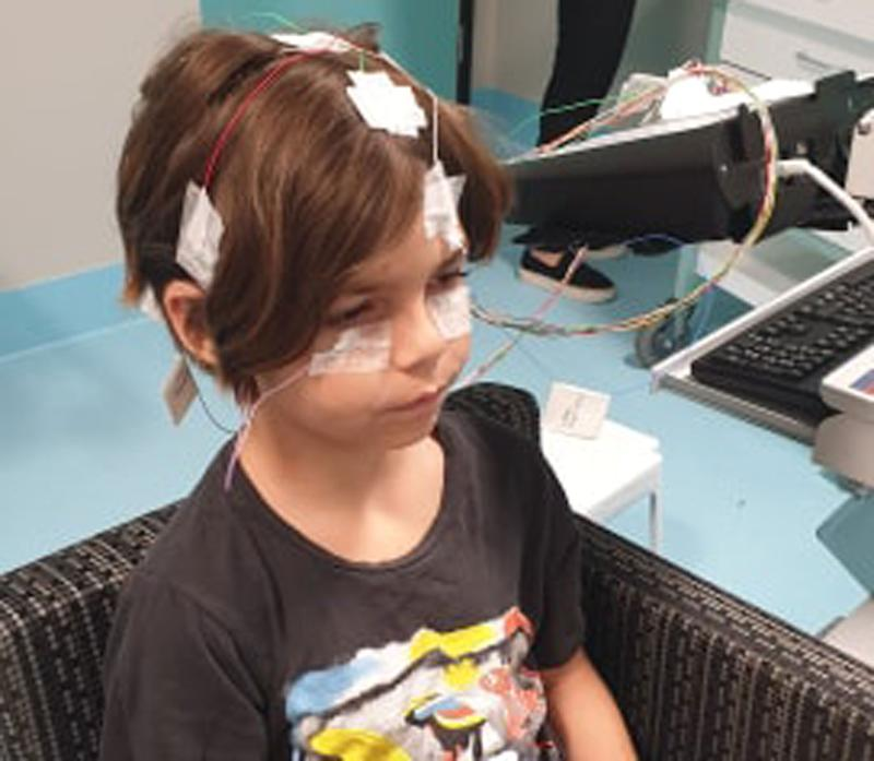 Theo Thomas, 8, is pictured with wiring and patches around his head. His mum says he will suffer permanent retinal damage.
