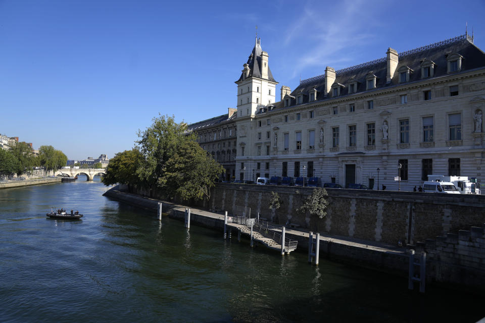 Police river forces patrol on the Seine river outside at the Palace of Justice, right, Wednesday, Sept. 8, 2021 in Paris. France is putting on trial 20 men accused in the Islamic State group's 2015 attacks on Paris that left 130 people dead and hundreds injured. The proceedings begin Wednesday in an enormous custom-designed chamber. Most of the defendants face the maximum sentence of life in prison if convicted of complicity in the attacks. Only Abdeslam is charged with murder. (AP Photo/Francois Mori)