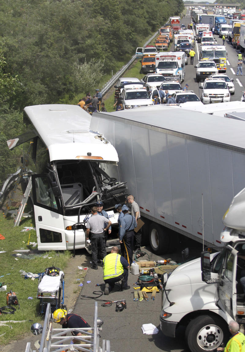 A tour bus on the New Jersey Turnpike collided with a tractor trailer, Wednesday, Aug. 24, 2011, South New Brunswick, N.J. Turnpike Authority Spokesman Tom Feeney says the crash occurred shortly after noon in the southbound lanes in South Brunswick. Feeney says preliminary reports show about a dozen people were hurt, with most of the injuries believed to be minor.    (AP Photo/Julio Cortez)